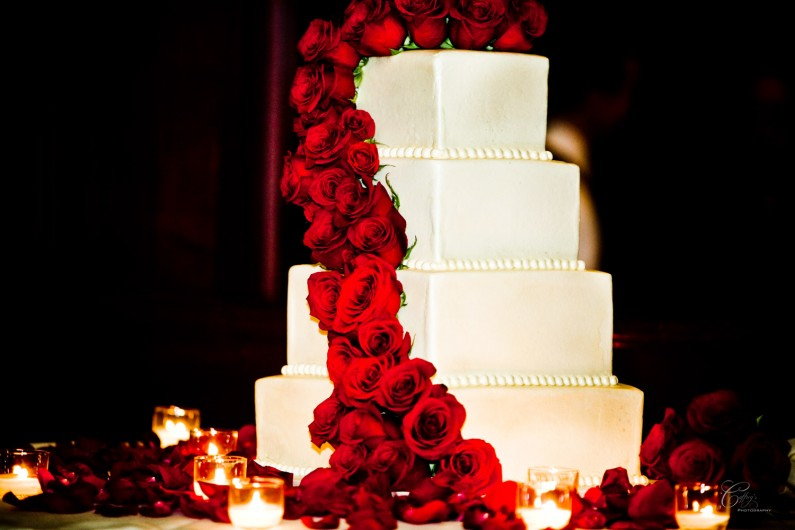 Gorgeous brides cake at her wedding with a cascade of beautiful red roses.