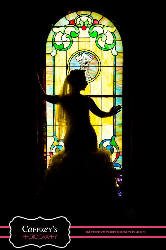 Breathtaking bride in silhouette by stained glass at Las Velas